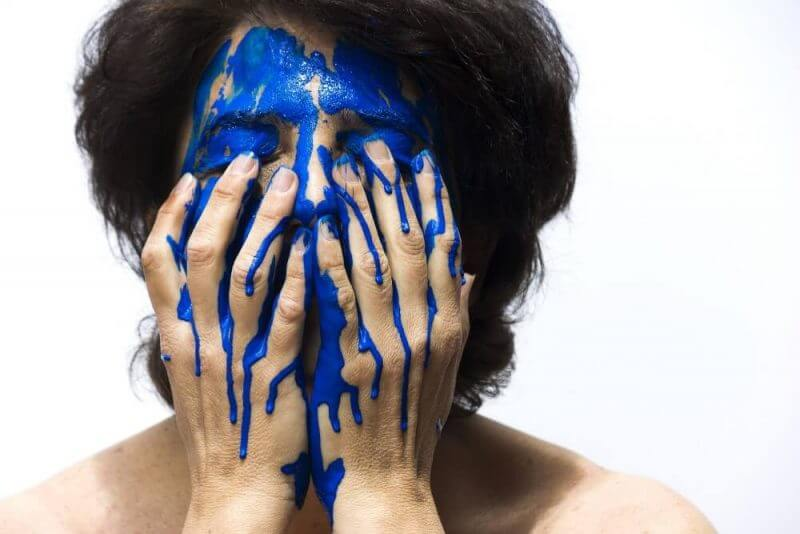 woman holding her face with blue substance on it