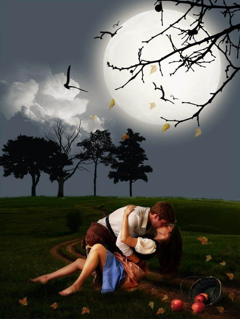 two kissing on grass outside under a moon at night