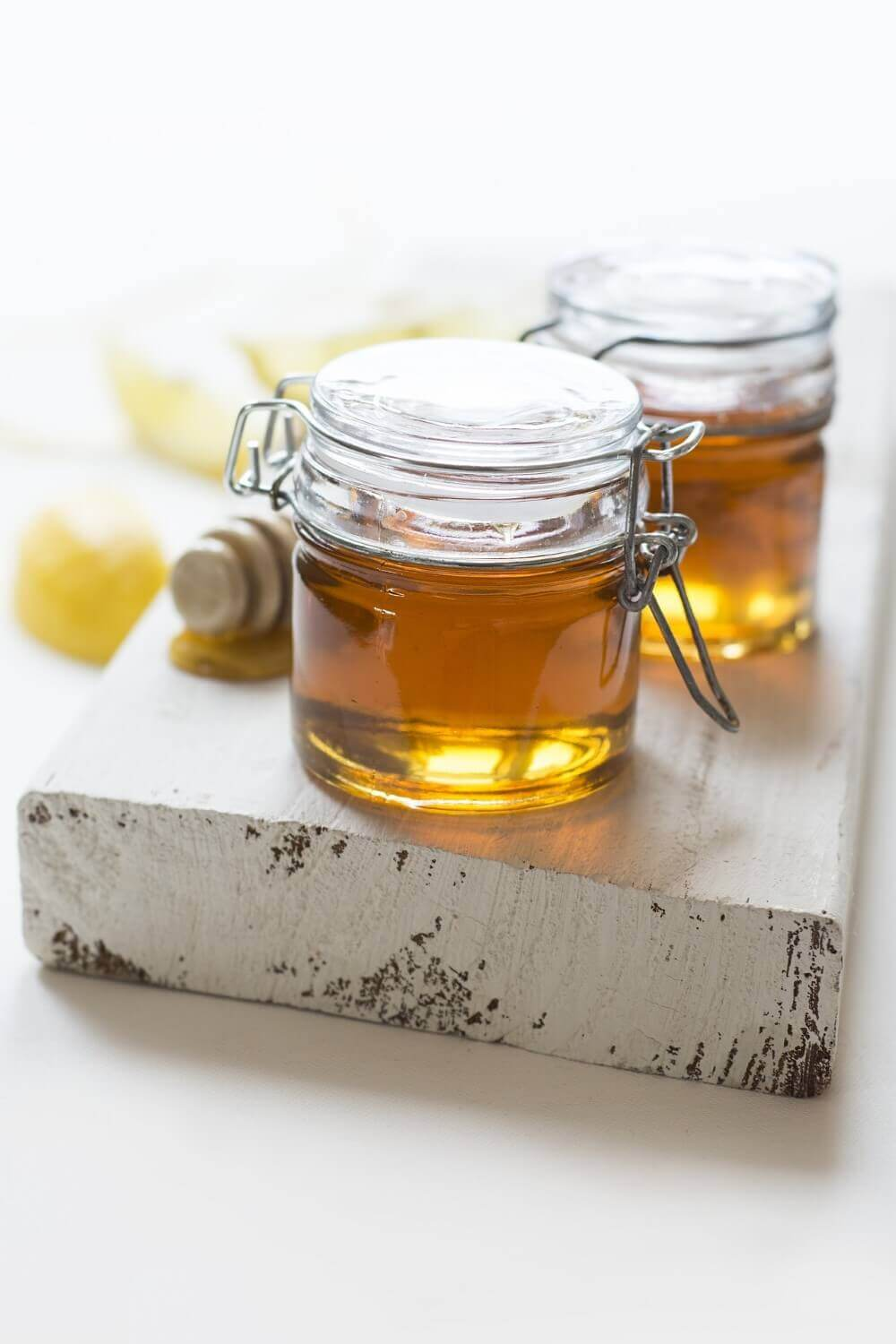 two glass cxans with honey inside