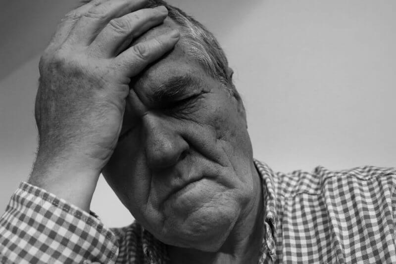 old man holding his head looking depressed