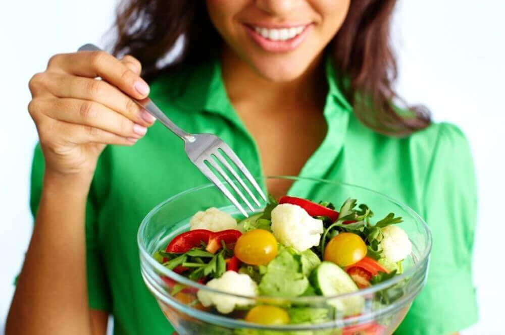 woman eating veggies from a bowl