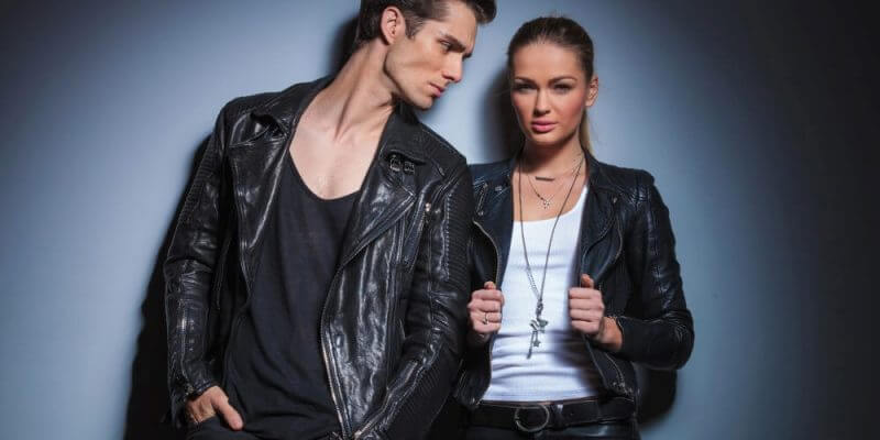 sexy fashionable man in black looking at his woman while she is posing for the camera arranging her jacket in studio background