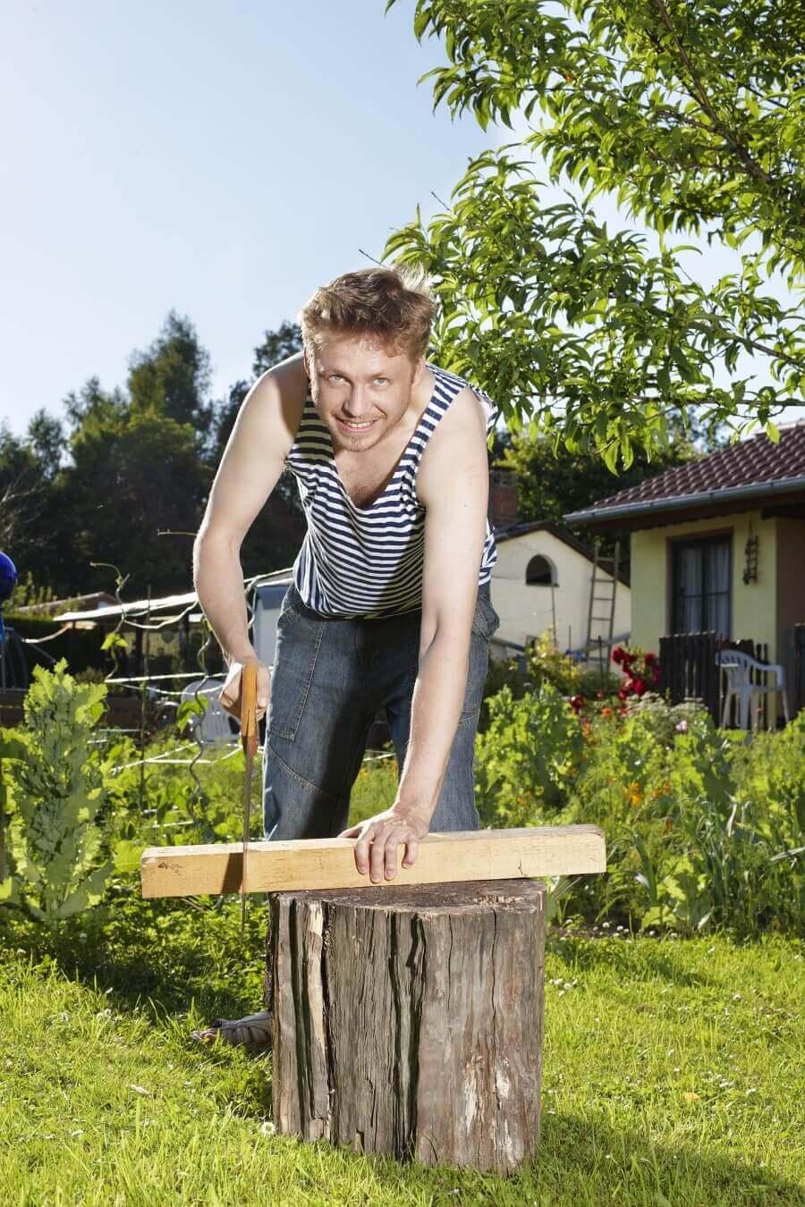 man cutting a piece of wood using a saw