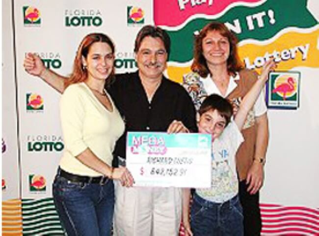 richard lustig with his wife, his son and his daughter holding the winning check