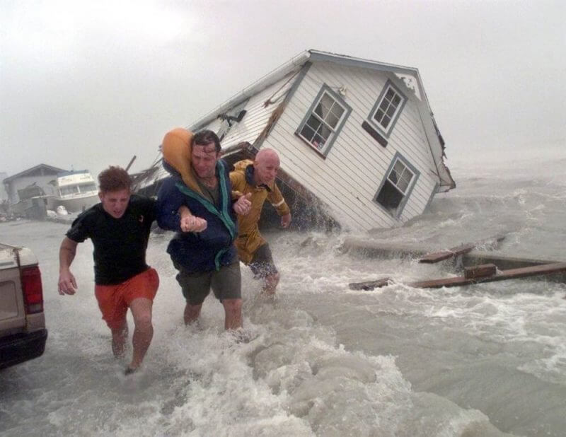 men running from a flooded home