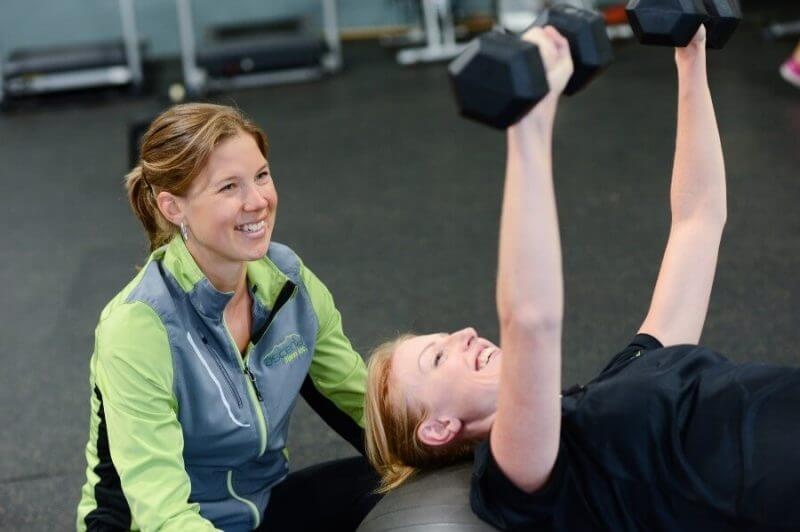 two women in a gym lifting weights