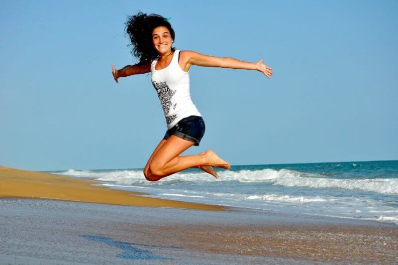lady jumping high with her hands open in the shore