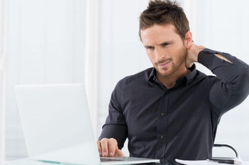 a man holds his neck while working on his laptop