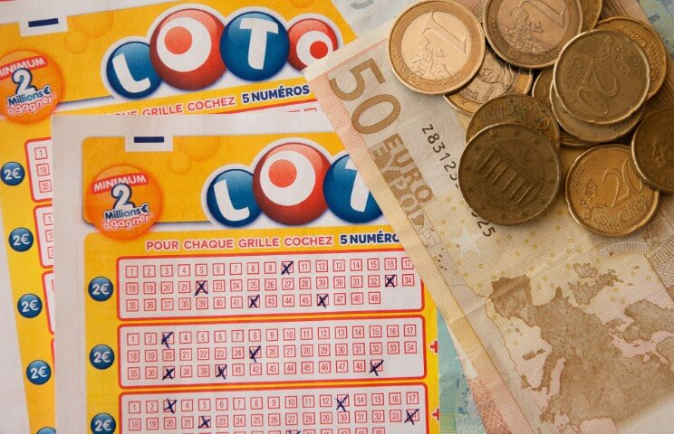 a filled in lottery ticket partially covered on the side by a 50 euro bill and coins