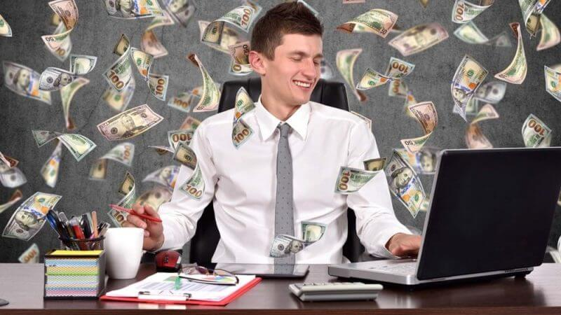 man working in an office and money notes in the background