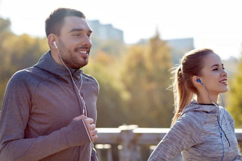 happy couple with earphones running in city