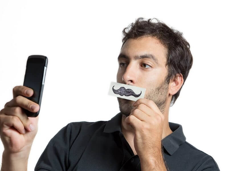 casual man make selfie portrait with fake moustache,  close composition isolated