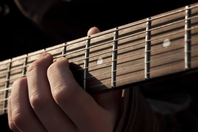 hand plucking guitar strings