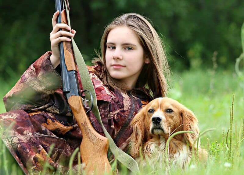 young girl with a rifle and a dog