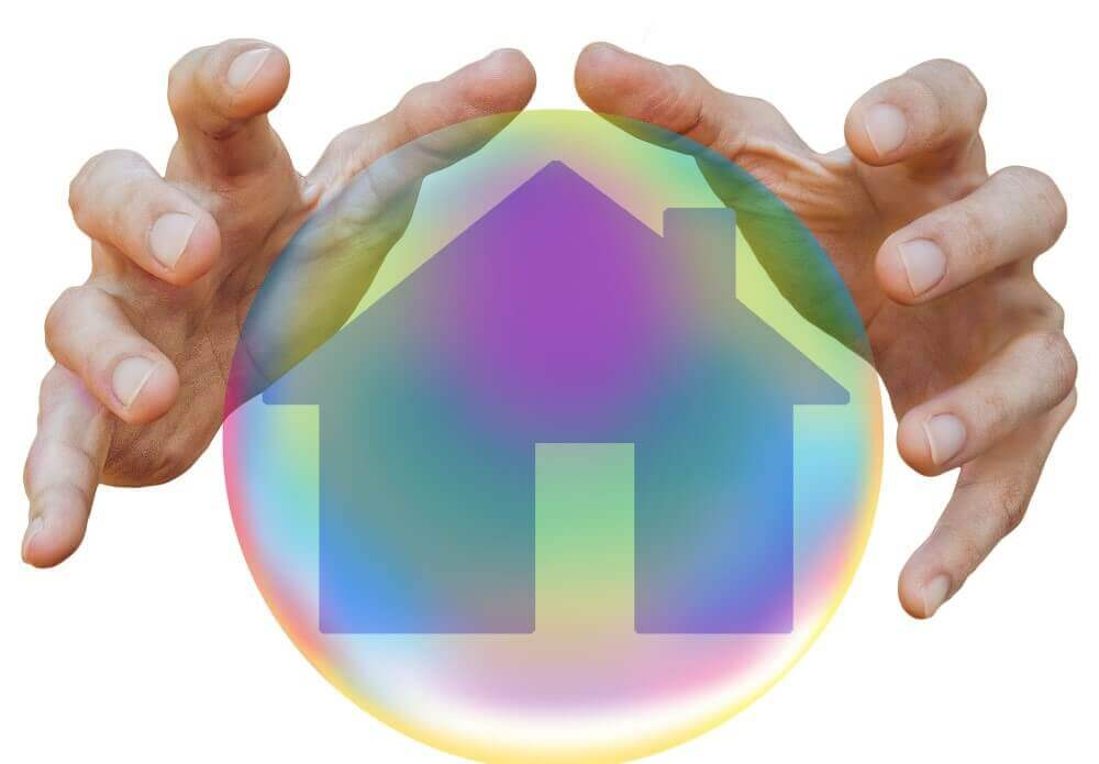 hands around a ball with a house