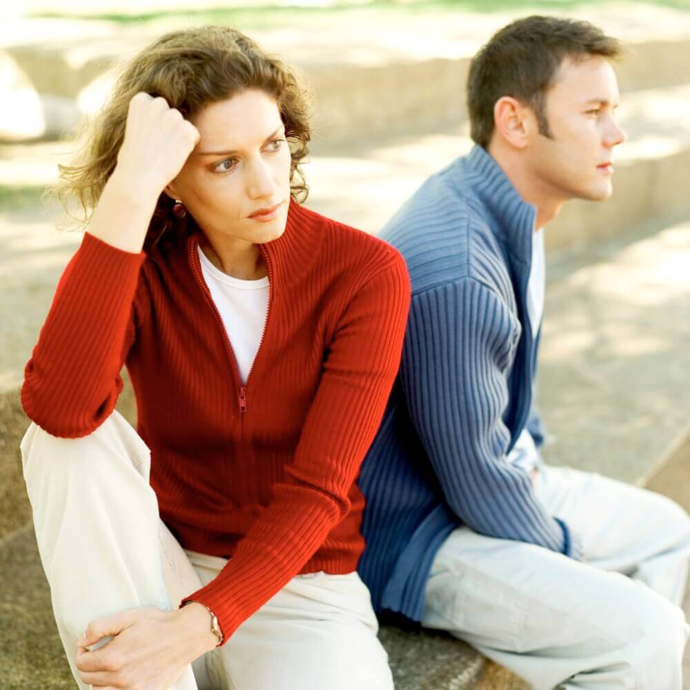 Young Couple Seated Back To Back --- Image by © Royalty-Free/Corbis