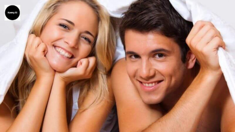 couples covering themselves in sheets looking happy