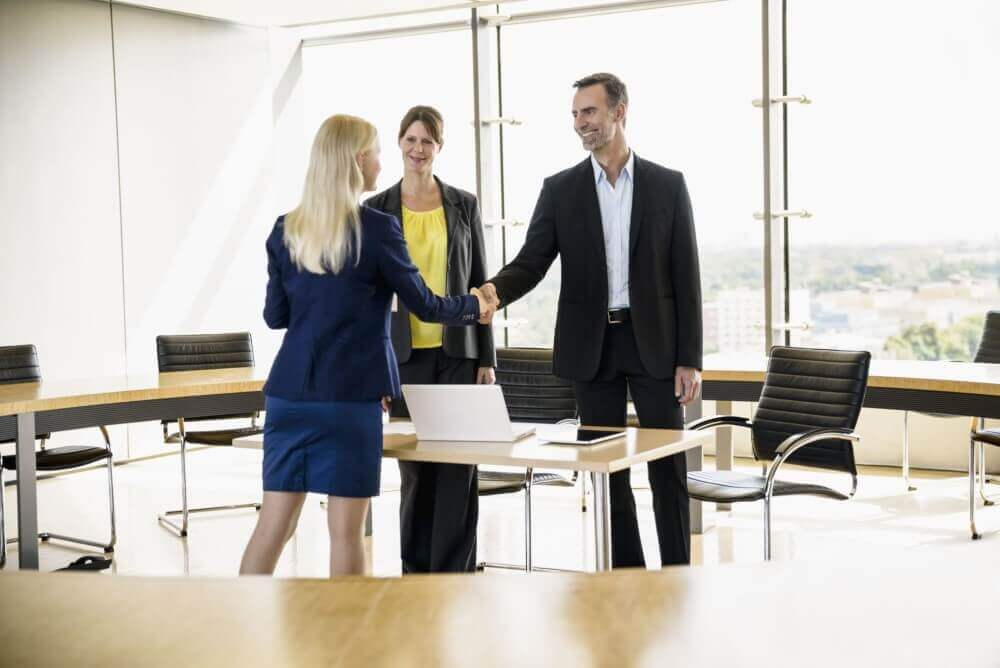 group of people shaking hand in an office