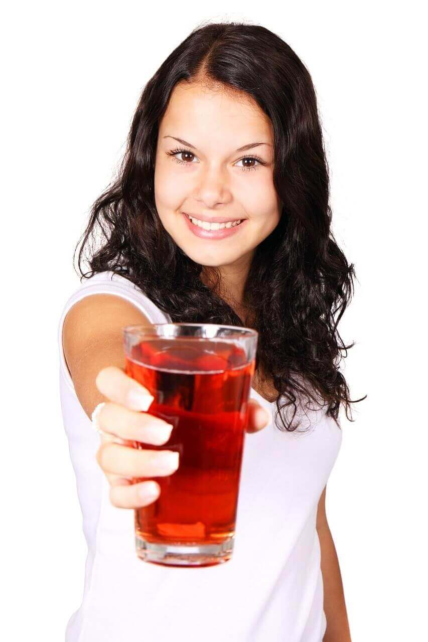 a cute lady holding a glass of juice