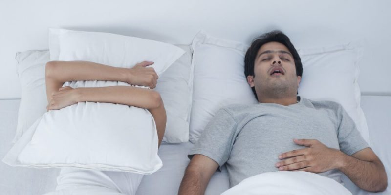 couple in bed and man snoring