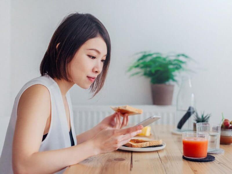 young lady using a phone and eating