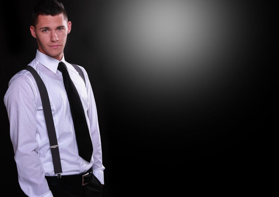 young man with a white shirt, black tie, black trousers and standing on a black background