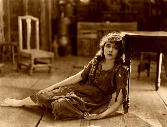 hungry retro woman sitting on the floor laying on the leg of a table
