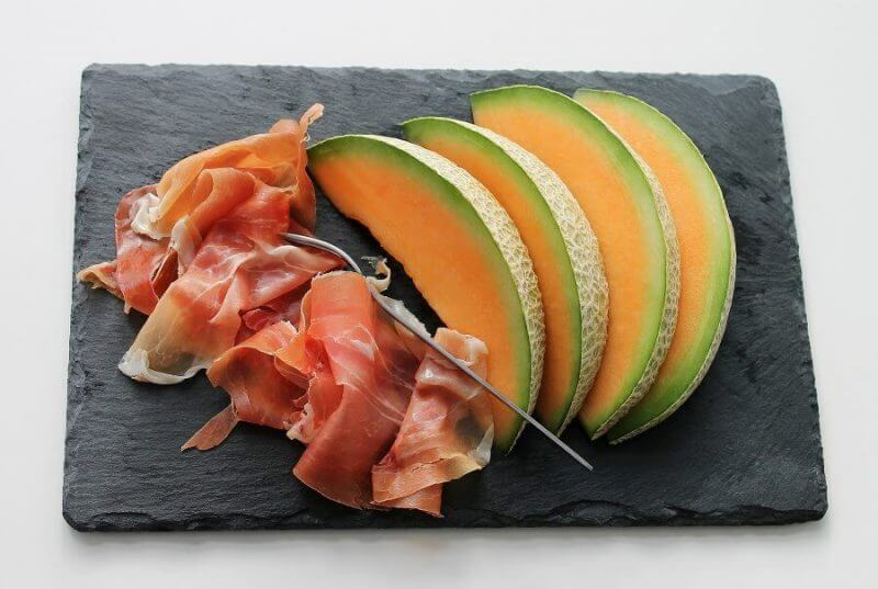 a fruit sliced into pieces on a chopping board