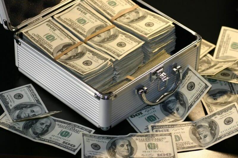 many dollar bills in a briefcase