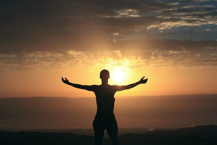 Instant Manifestation Secrets woman on top of a hill with arms wide open to the sun set