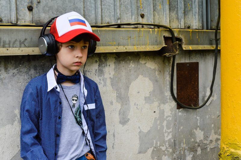 a little boy with a can and headphones on his ears, laying behind a wall