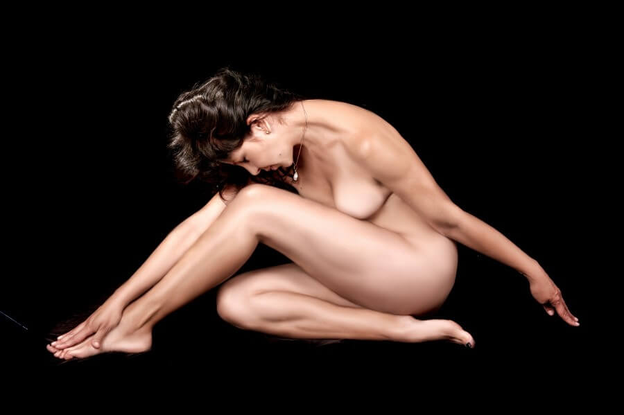 naked woman seated on a black background