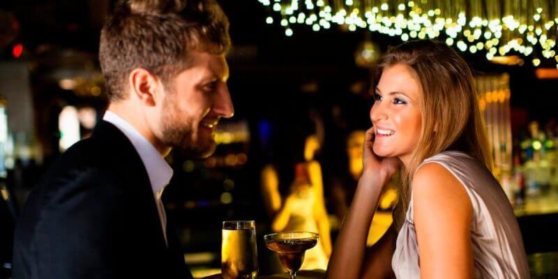 Smiling couple having drinks at bar