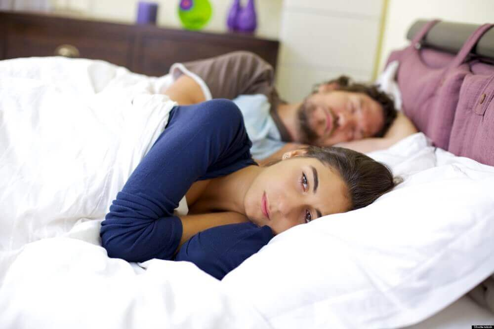 couple sleeping looking sad