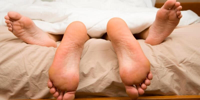 View of feet of couple having sex in bed.