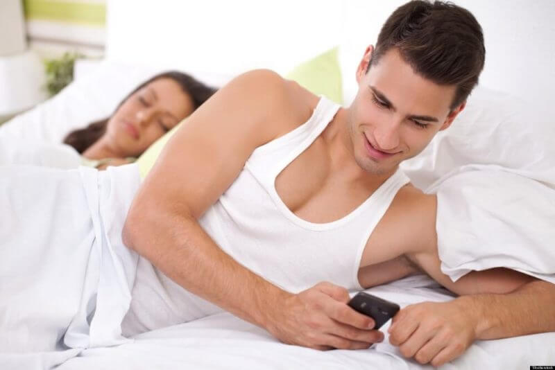 man cheating by texting in bedroom