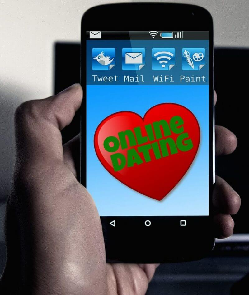 hand holding smartphone showing online dating on the screen