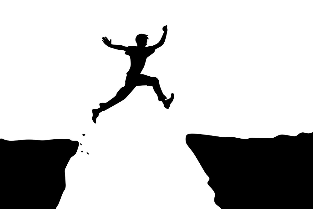 man jumping from the cliff to another