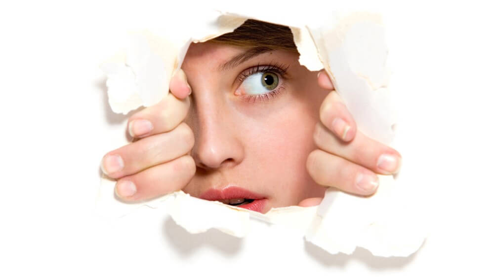 shy woman looking through a white torn paper