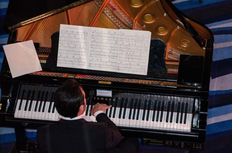 a man reading the tonal scale's while playing the piano