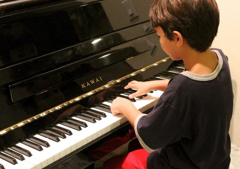 boy playing piano for all