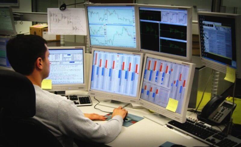 a forex trader behind many computer screens