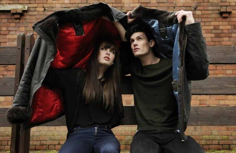 lovers seated and covering themselves in jackets
