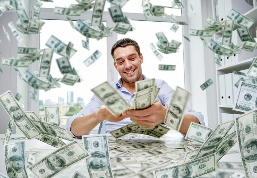 happy succcessfull businessman with piles of cash