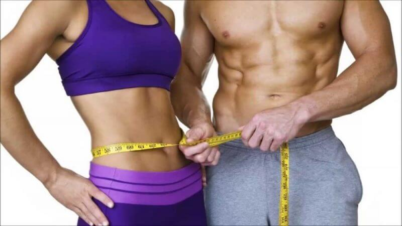 man measuring woman waist