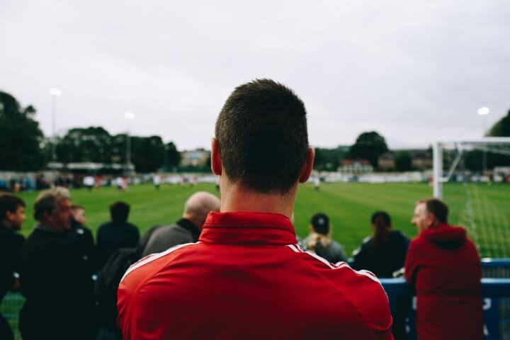 Throughbred Betting represented by a man in a red shirt watching a football game in the stadium