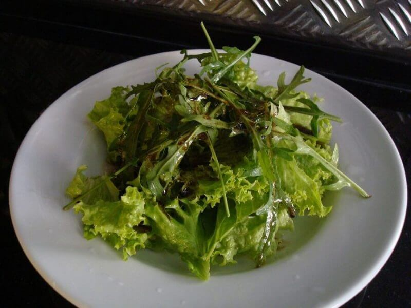a white plate with some green leaves