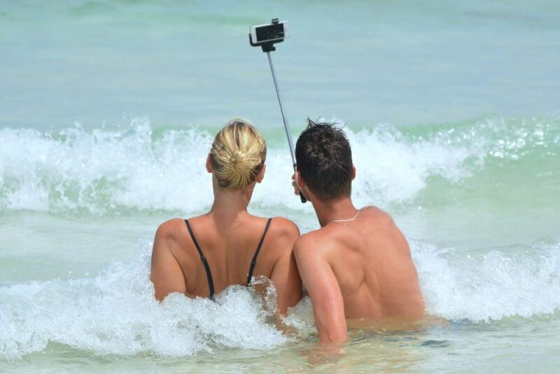 two couples taking photo with a selfie stick