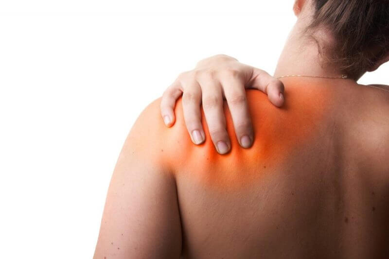 Young woman with sever back pain. She is holding her shoulder. Over white background. The hurting area was saturated in red to symbolize the pain.