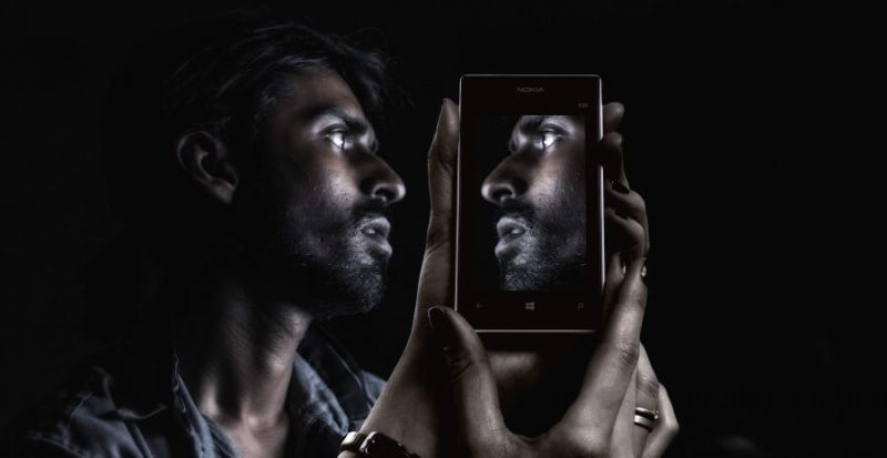 a man looking at himself on a phone's screen